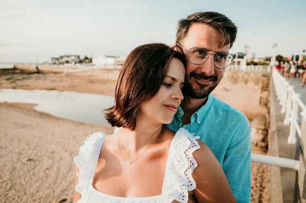 Беременная пара фотографирует на пляже на закате