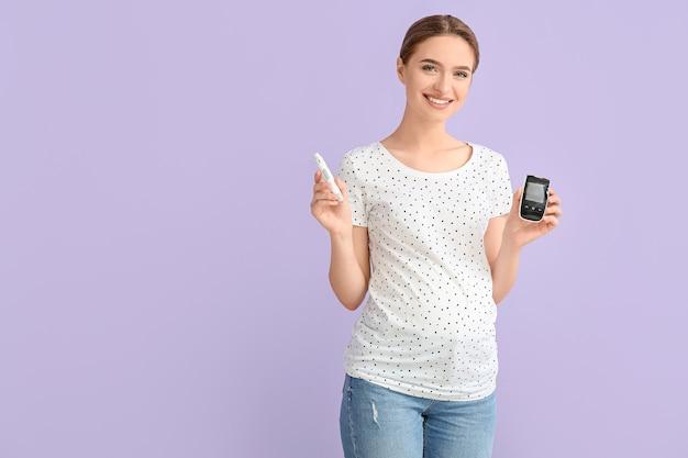 Беременная женщина-диабетик с цифровым глюкометром и ланцетной ручкой на цветной поверхности
