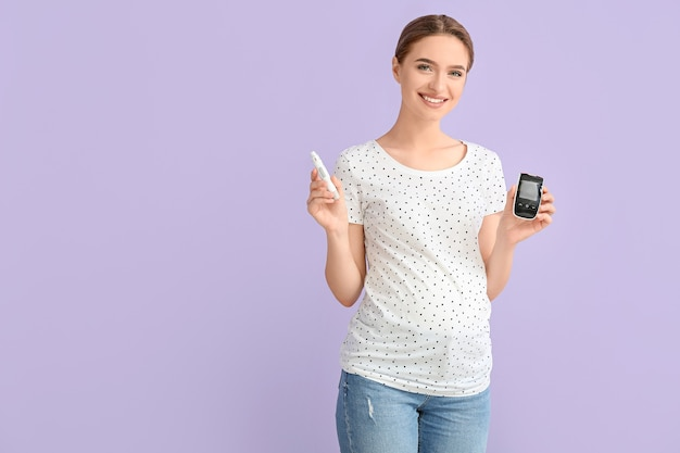 Pregnant diabetic woman with digital glucometer and lancet pen on color surface