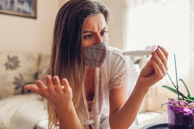 Беременность во время коронавируса ковид-19. больная женщина в маске проверяя тест на беременность дома.