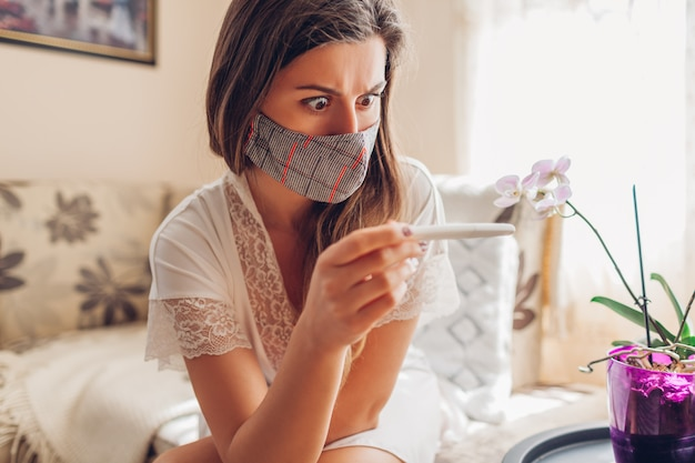 Pregnant during coronavirus covid-19. ill woman in mask checking pregnancy test at home.