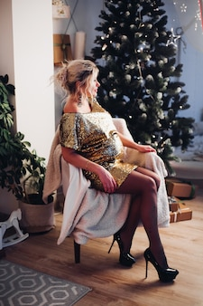 Pregnant elegant woman in arm-chair against christmas tree.