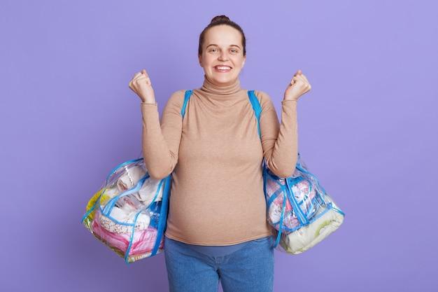 Pregnant european woman with hair bun leaving for maternity hospital