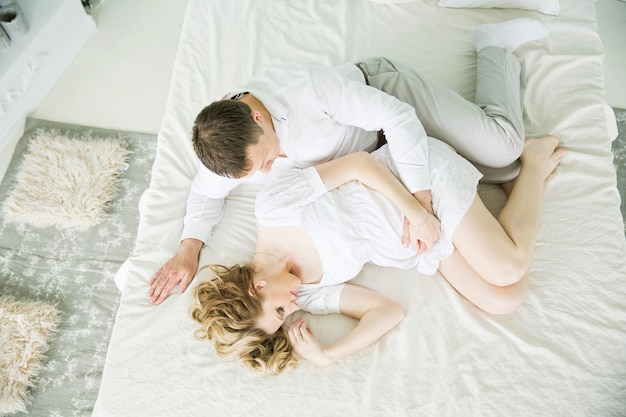 Беременная семья лежит на кровати дома.