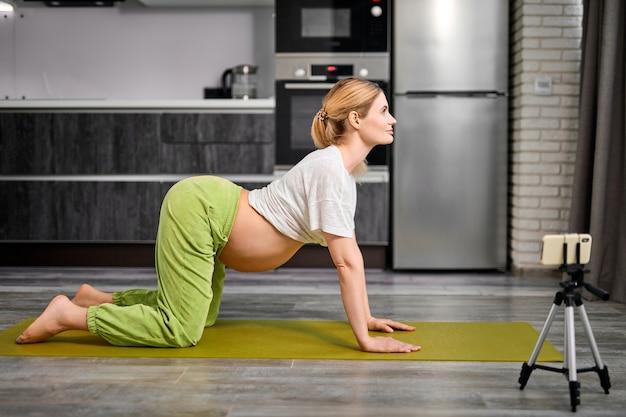 猫のポーズをしている妊婦が自宅でビデオオンラインレッスンを見てmarjariasana運動をしている