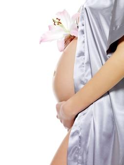 白で隔離のかわいい腹と花を保持している妊娠中の女性。