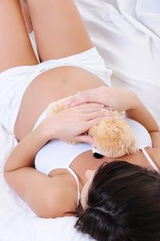 Беременная женщина, лежа на белой кровати с игрушкой тедди