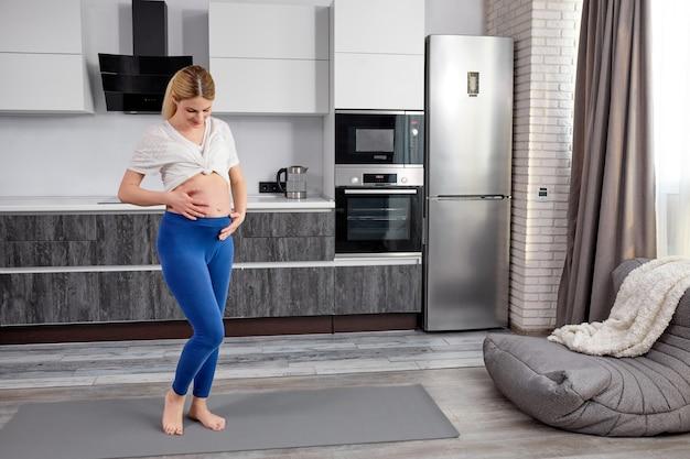 Беременная женщина стоит на коврике для упражнений и касается ее живота, готовая к пренатальным упражнениям йоги