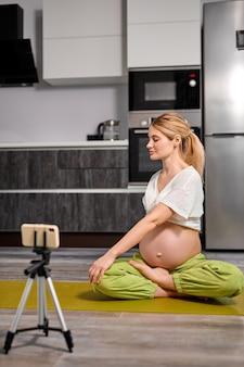 Беременная женщина растягивает тело дома, собирается делать упражнения йоги на полу