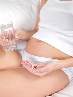 Pregnant female with glass of water and tablets in hands