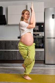 Беременная женщина с голым большим животом практикует упражнения йоги, стоя на одной ноге