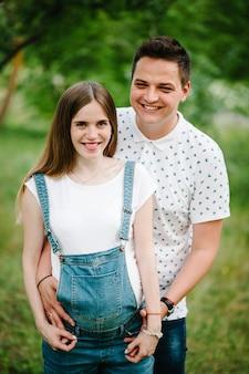 妊娠中の女の子と彼女の夫は幸せです、胃に手をつないでください。閉じる。上半分。カメラ目線