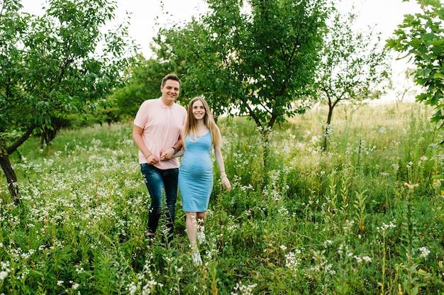 Беременная девушка и ее муж с удовольствием держатся за руки, гуляя на свежем воздухе в саду