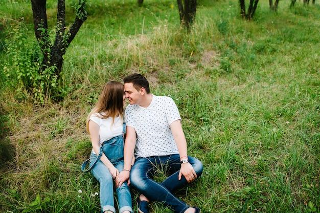 妊娠中の女の子と彼女の夫は、庭の表面の屋外の芝生に座って、抱きしめ、胃に手を握って喜んで