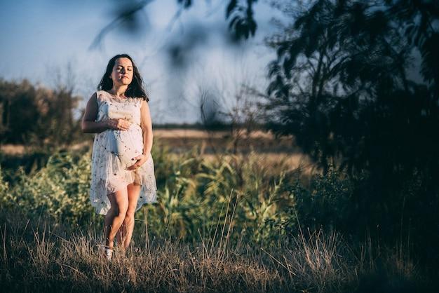 혼자 자연 속에서 느슨한 드레스에 일몰에 임신한 여자