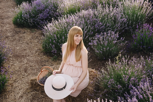 베이지 색 드레스와 밀 짚 모자에 임신 한 여자 금발. 라벤더 밭. 아이를 기대합니다. 사진 촬영의 아이디어. 일몰 도보. 미래의 엄마. 꽃 바구니.