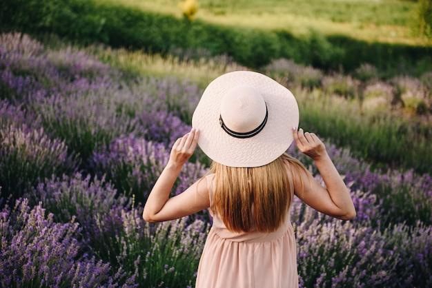 Беременная девушка блондинка в бежевом платье и соломенной шляпе. лавандовое поле. в ожидании ребенка. идея фотосессии. прогулка на закате. будущая мама