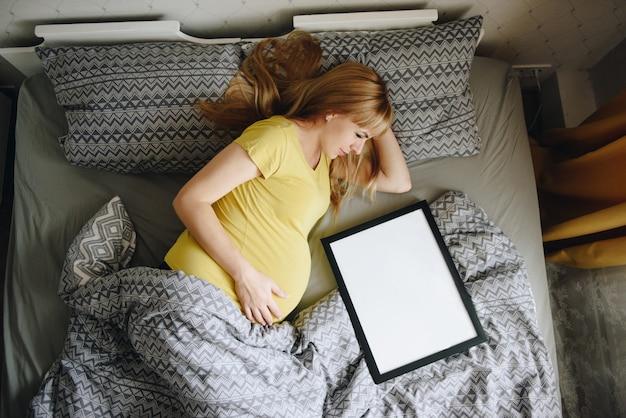妊娠中の女の子金髪の黄色いtシャツを自宅で。奇跡を待つ。妊娠。愛と希望。明るい部屋。寝室のベッドにあります。テキストのフレーム。グレーの寝具。