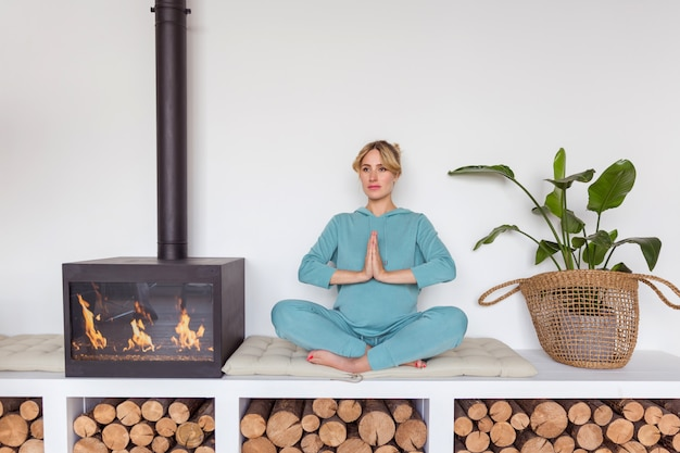 Pregnant girl in blue sportswear sits in lotus position doing yoga in cozy interior