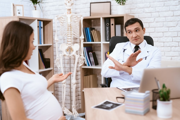 Pregnant girl and doctor talk seriously in doctor's office.