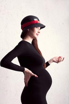 Беременная девушка, одетая в черное платье и шляпу, держит себя за спину