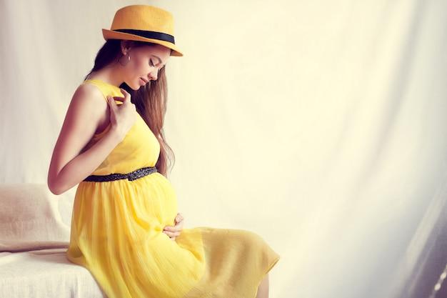 Беременная девушка, одетая в желтое платье и шляпу, сидит на кровати и держит животик