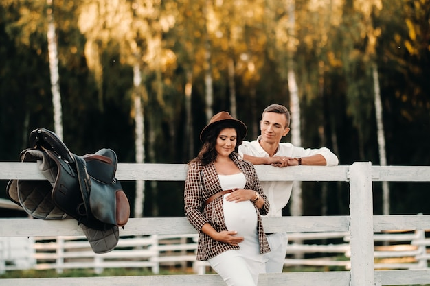 A pregnant girl in a hat and her husband in white clothes stand next to a horse corral at sunset.