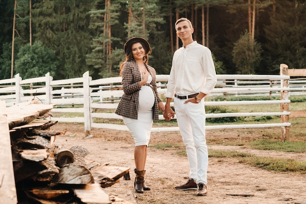 A pregnant girl in a hat and her husband in white clothes stand next to a horse corral at sunset