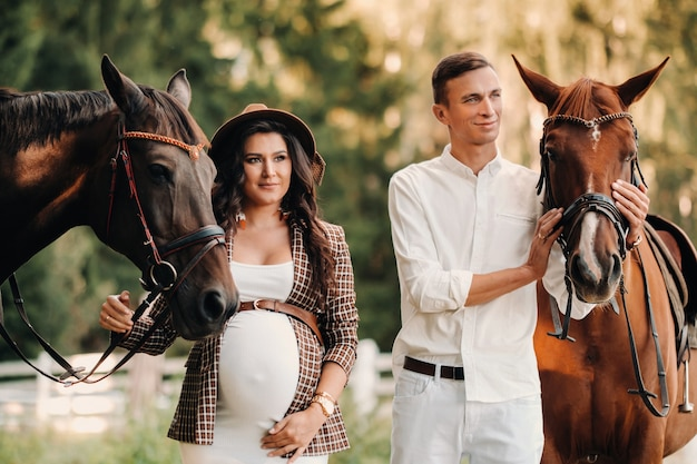 A pregnant girl in a hat and her husband in white clothes stand next to horses in the forest in nature.stylish pregnant woman with a man with horses.family.