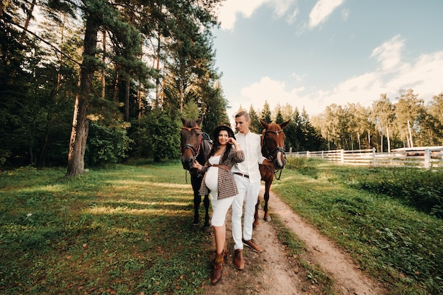 A pregnant girl in a hat and her husband in white clothes stand next to horses in the forest in nature.