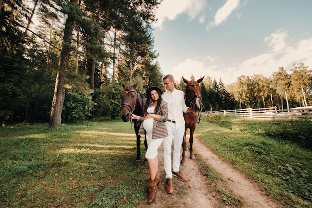 A pregnant girl in a hat and her husband in white clothes stand next to horses in the forest in nature