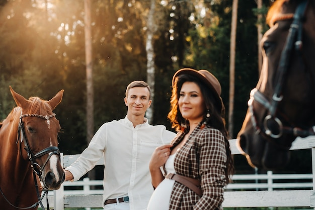 A pregnant girl in a hat and her husband in white clothes stand next to the horses near the horse corral.stylish pregnant woman with a man with horses.family.