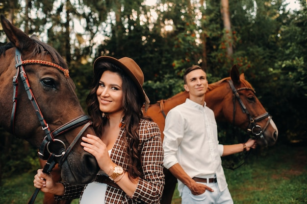 A pregnant girl in a hat and a man in white clothes stand next to horses in the forest in nature.stylish pregnant woman with her husband with horses.married couple.