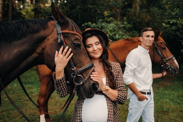 A pregnant girl in a hat and a man in white clothes stand next to horses in the forest in nature.