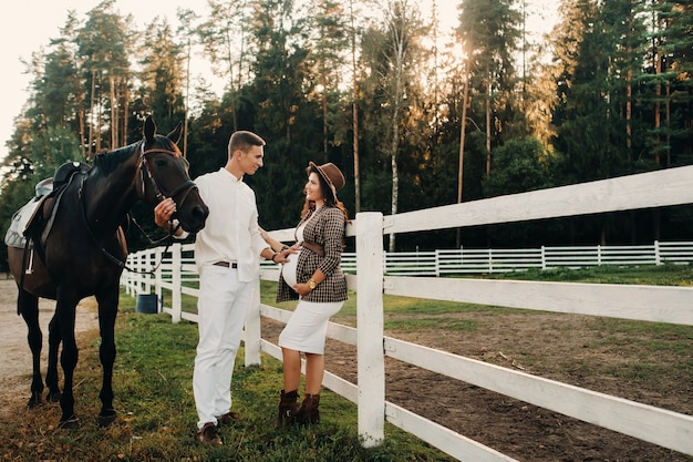 A pregnant girl in a hat and a man in white clothes stand next to horses near a white fence.stylish pregnant woman with a man with horses.married couple.