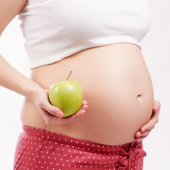 Pregnant girl holding a green apple