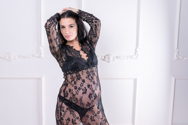Беременная девушка в черном пеньюаре. фото высокого качества