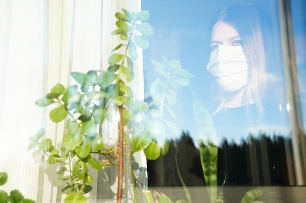 의료용 마스크를 쓴 임신 한 소녀가 코로나 19 유행성 창밖으로 보인다