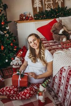 크리스마스 트리 근처 잠옷에 임신한 여자입니다. 새해
