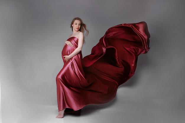 밝은 배경에 빨간 드레스 아름다운 패브릭 질감에 임신한 여자