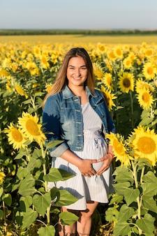 ひまわりの妊娠中の女の子、赤ちゃんを待っている幸せな女の子