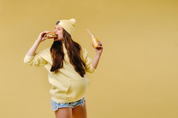 黄色の背景にハンバーガーを手に黄色い服を着た妊婦