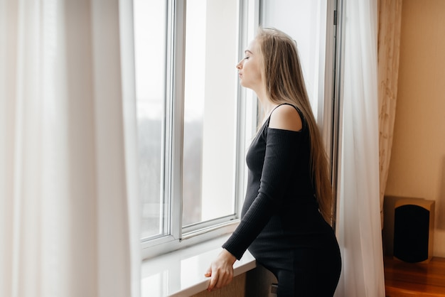 A pregnant girl is breathing fresh air from the window