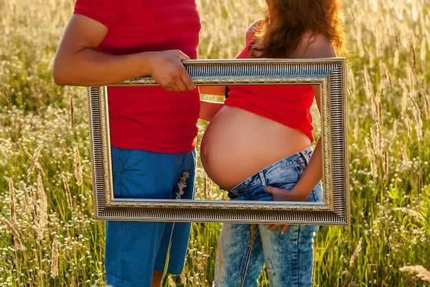 Pregnant girl in nature. photoshoot of a pregnant girl in jint and red t-shirt in a field at sunset. the girl is photographed with a frame for pictures