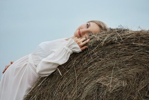 長い白いドレスを着た干し草の山に妊娠中の女の子、女性は微笑み、胃に手を当てる