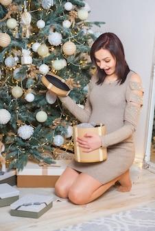 妊娠中の女の子がクリスマスプレゼントを開きます