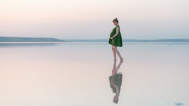 Pregnant girl posing at sunset in the water with a reflection. amazing sunset over a shallow lake.