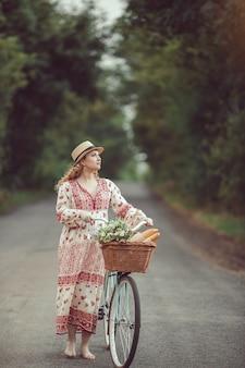 Беременная девушка ретро французском стиле с велосипедом на лесной дороге