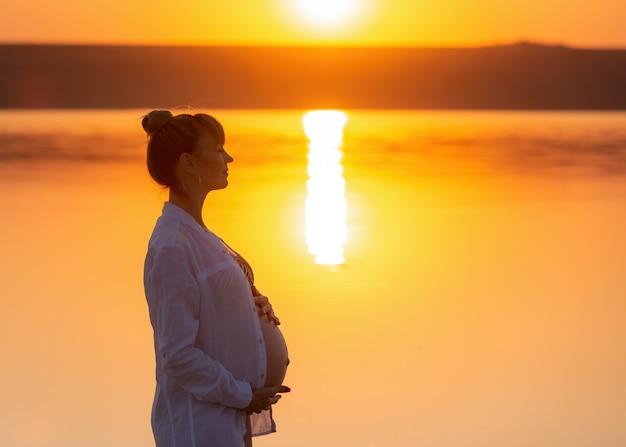 妊娠中の女の子の横顔のシルエット。女の子は遠くを見て、おなかに触れます。夏の夕焼け空の屋外でリラックス