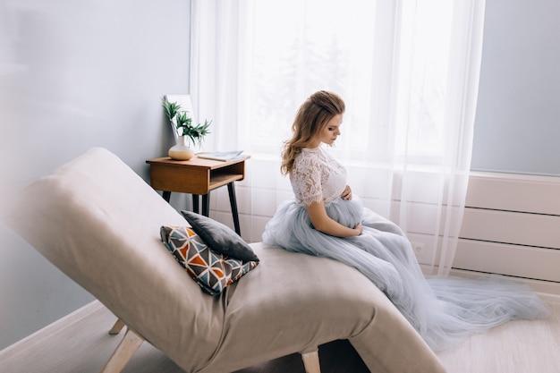 임신 한 여자는 장식 된 의자에 앉아